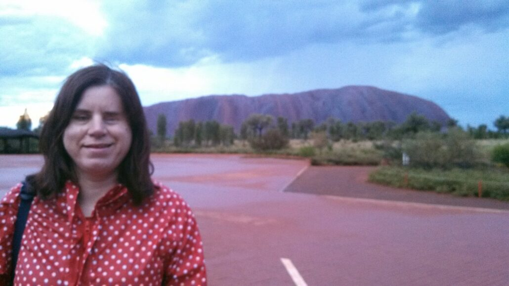 Ffion smiles, the vast expanse of Uluru rising behind her under a partly cloudy blue sky.