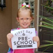 """A young smiling girl holds a certificate that states """"First Day of Pre-School 2018-2019""""."""