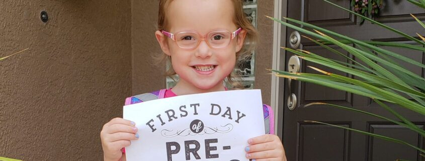 "A young smiling girl holds a certificate that states ""First Day of Pre-School 2018-2019""."