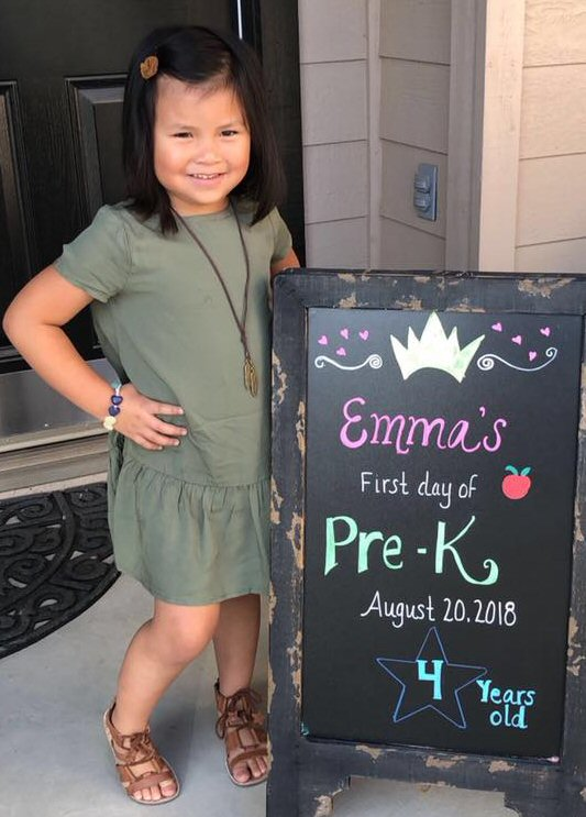 "A young girl stands next to a blackboard that states ""Emma's first day of Pre-K, August 20, 2018. 4 years old."""