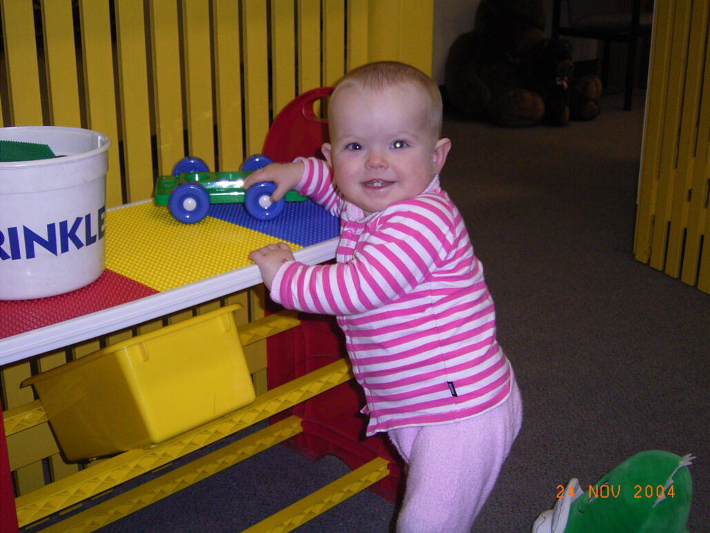 A toddler stands at a brightly coloured low unit, playing with some toys.