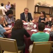 Two small group discussions are taking place around separate tables.