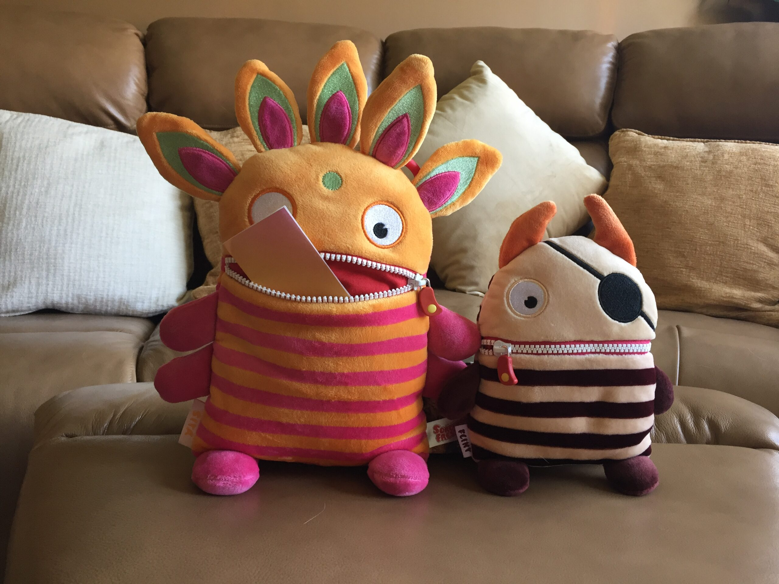 Two whimsical plush characters stand next to one another on a caramel coloured leather footstool in front of a matching sofa covered in cushions of varied natural colours. Both plushes have horizontal striped bodies of alternating colours, big round eyes and a zip mouth. Sita on the left is about one third taller, and has five protrusions from the top of its head that look like flames, each coloured pink, white and light orange. It has small pink round feet and butterfly wings, its body stripes are pink and light orange, and its face is light orange, with a light blue spot in the centre of its forehead. Its mouth is unzipped, holding a piece of rainbow coloured paper. On the right, Flint's stripes are coloured chocolate and latte, with a latte coloured face and chocolate coloured hands and feet. A pirate patch covers the left eye, and two caramel coloured horns curl gently towards one another, the left one slightly longer than the right.