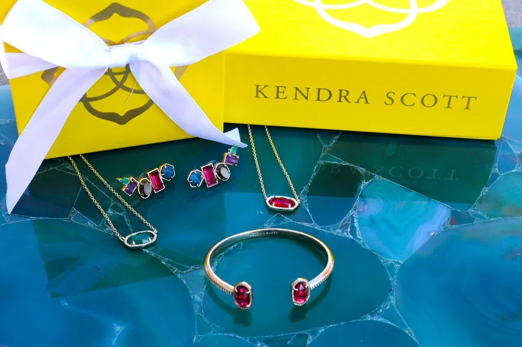A yellow Kendra Scott jewelry box with a white ribbon sits on a turquoise blue cloth with an assortment of jeweled earrings, pendents and bracelets.