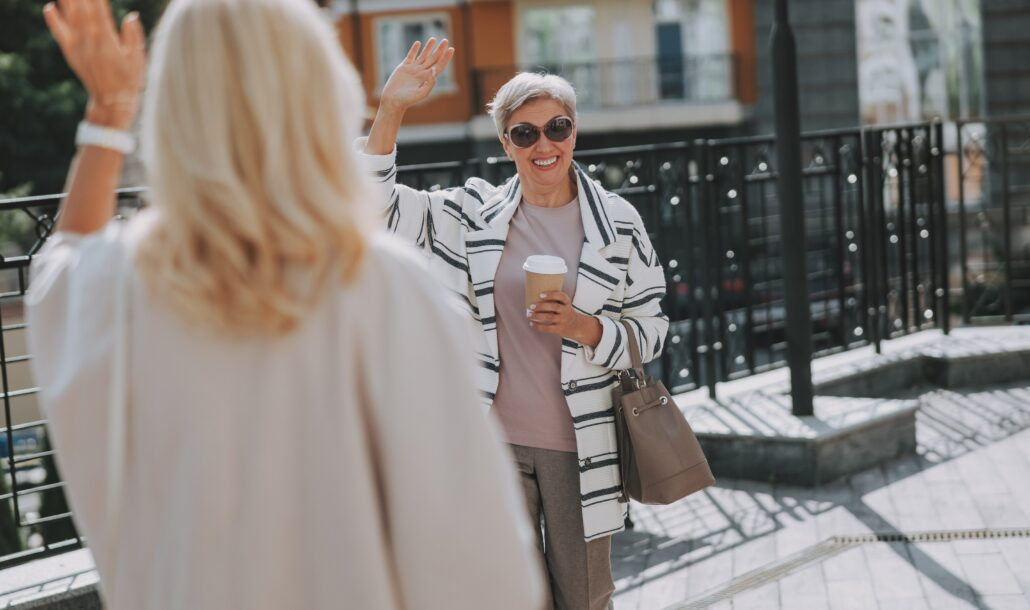 Two women stand on a street. In the foreground is a woman's back and long light-blond hair; her left hand is raised up waving. In the background, a white-haired woman wearing sunglasses is facing the camera, holding a cup of coffee and waving at the first woman. There appears to be several feet of space between them.