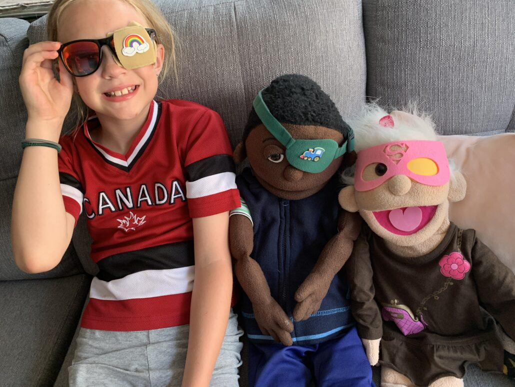A young girl sits on a couch next two two life-size puppets. They are all wearing different types of eye patch. The child has a patch over one lens of her sunglasses. One puppet wears a patch on a band, and the other wears a superhero mask with one eye hole covered up on the inside.