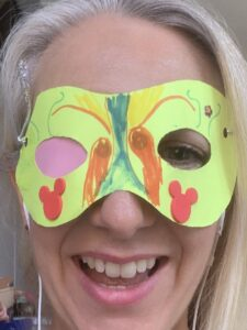 Morgan is smiling and wearing a homemade superhero mask with one eye hole covered over on the inside of the mask with pink paper.