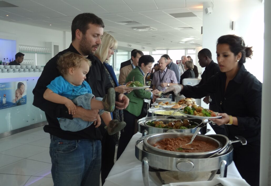 People gather around a buffet table laden with food. In the foreground, a woman on one side of the table places food on a plate while in conversation with a gentleman on the other side of the table who is holding a young toddler. Off to the side, a poster advertises a retinal camera from Clarity Medical.