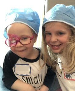 Two siblings stand shoulder to shoulder, smiling. One sister wears an eye patch over one eye behind her glasses.