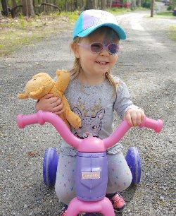 A child wearing an eye patch has fun rideing a bike.