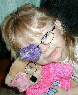 A child wearing an eye patch hugs her teddy bear, who is also wearing a patch over one eye.