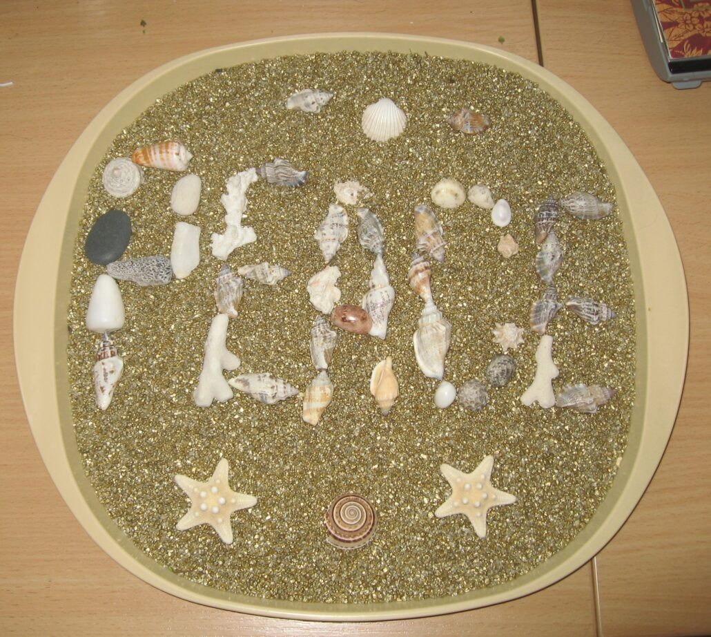 A shallow round tray is filled with glittering gold sand. The word PEACE is spelled out in many different shells, sea stars and pieces of coral, and the entire piece is finished off with several shells and sea stars decorating the top and bottom.