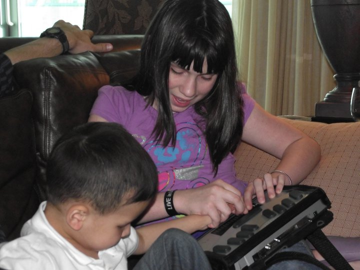 Using both hands, a schoolgirl guides the hand of a younger boy in exploration of a Perkins brailler.