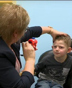 A child looks at the tiger being held aloft by an orthoptist. The orthoptist's other hand rests on the child's head to help him keep it still.