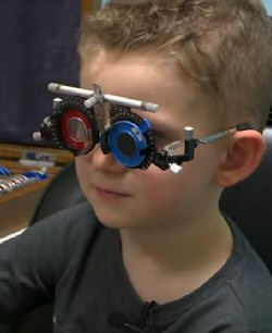 A young boy wears special glasses with different lenses to assess his vision.
