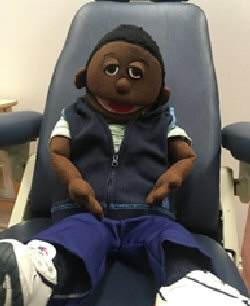 A medical play puppet sits in a big examination chair.