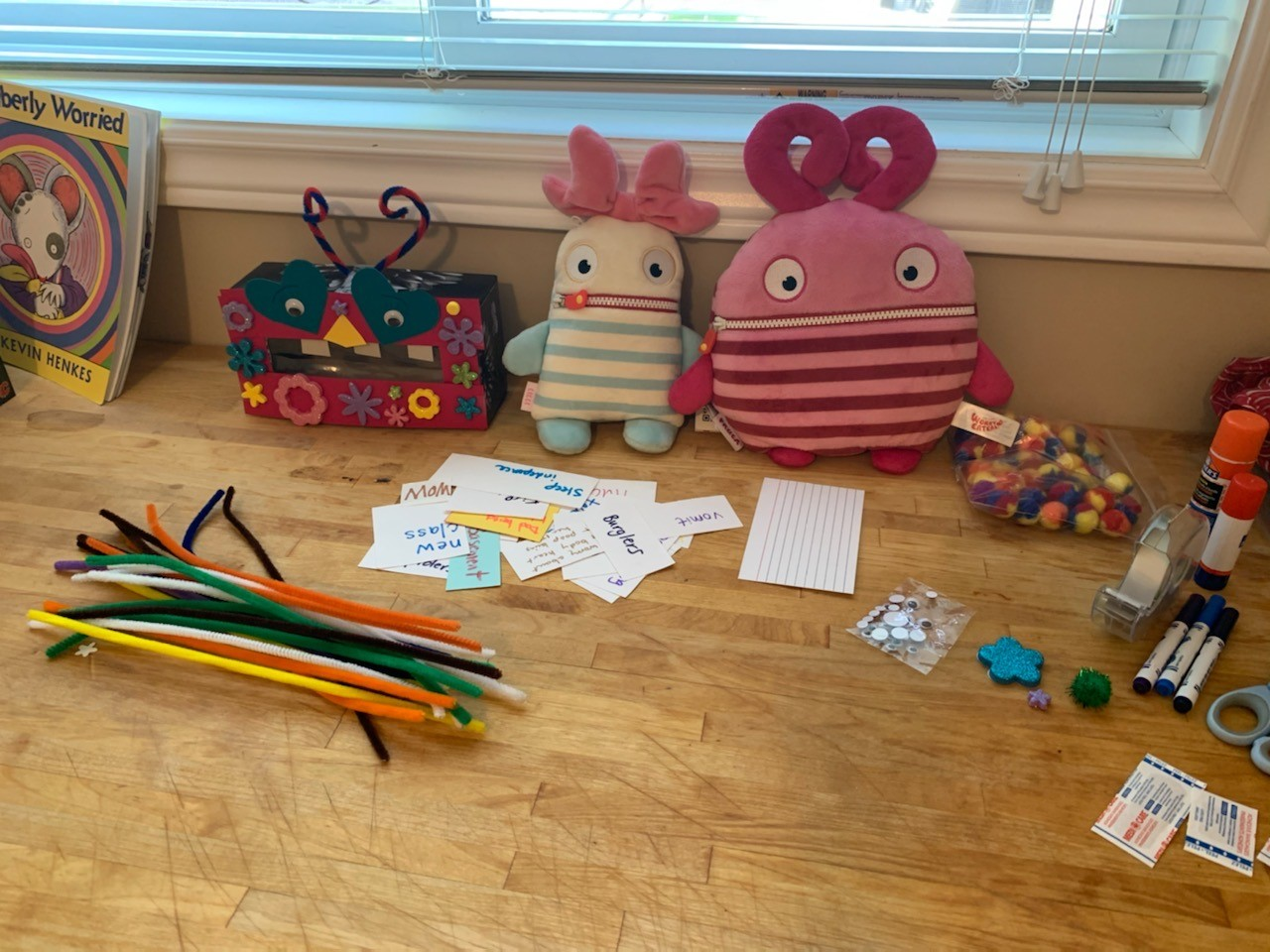 Several worry eater plush toys and a homemade worry eater box sit among a selection of craft materials prepared for a worry eater making activity.