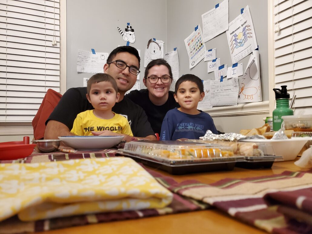 A young girl, father, mother and young son are seated at the holiday thanksgiving table with take-out trays containing their favorite restaurant foods on the table in front of them. Hanging on the wall behind the family is the children's art work and school activity pages.