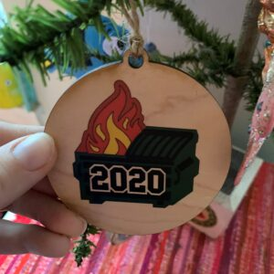 """Close up of a wooden decoration depicting a burning dumpster that says """"2020"""" on it, hanging on a feather Christmas tree."""