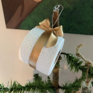 Close up of toilet roll tied with gold bow, at the top of a feather Christmas tree
