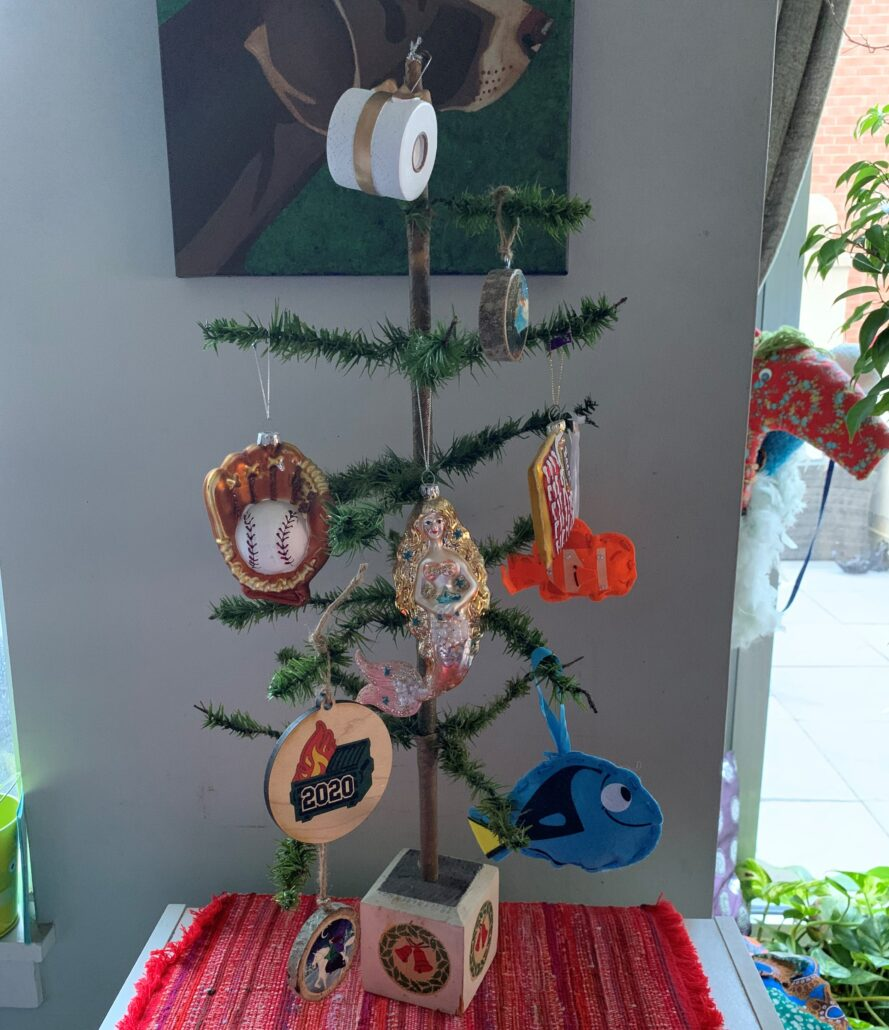 """A simple feather tree is decorated with traditional and home-made ornaments, including several depicting the 2020 COVID-19 pandemic. A toilet paper roll with a good bow takes top place. Next level down are 3 glass ornaments of a baseball glove, a mermaid, and bacon. Next level down, a wood decoration with a painting of a trash dumpster that is on fire, with """"2020"""" written on the front. To the right are two hand sewn decorations of fish, Nemo and Dory from the Finding Nemo movie."""