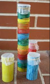 Three colourful rainsticks of different heights stand in front of a brick wall.