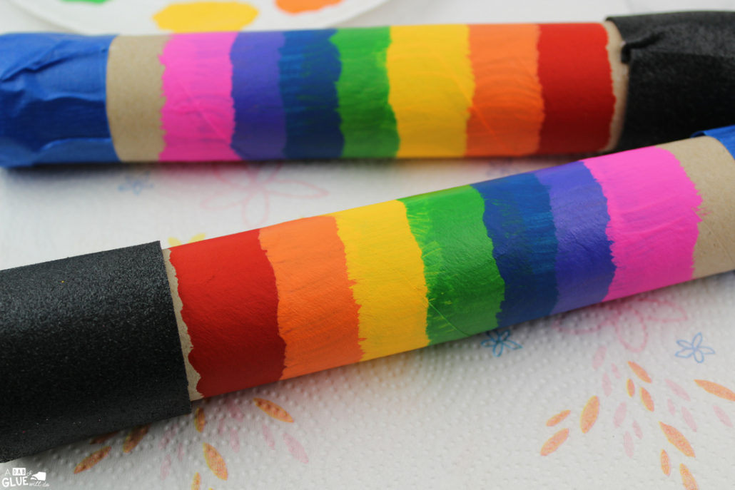 Two brightly coloured rainbow rain sticks laying on their sides