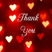 """The words """"Thank You"""" are written in script on a dark red background infused with light, surrounded by glowing red, gold and white love hearts."""