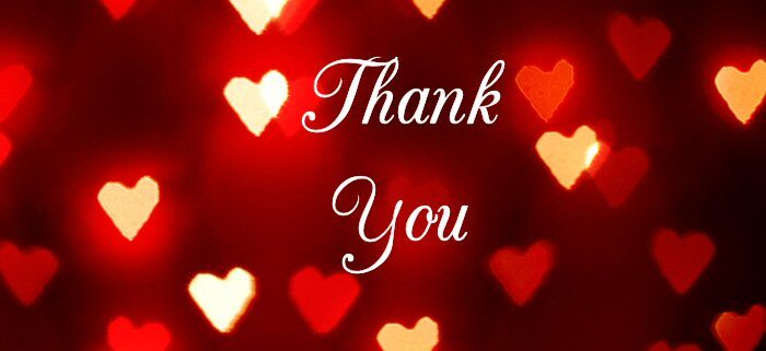"The words ""Thank You"" are written in script on a dark red background infused with light, surrounded by glowing red, gold and white love hearts."