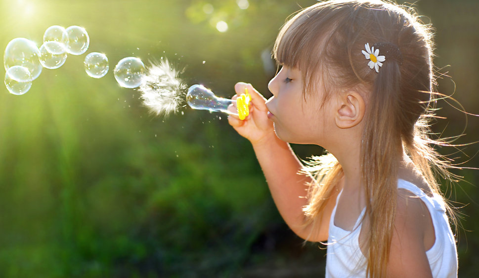 A young girl blows bubbles with a buble wand.
