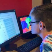 A young teenage boy wearing glasses leans in towards a large computer screen on the desk in front of him. Text on the screen has been blurred for privacy. A smaller screen sits on his right, and an iPad can be seen to his right.