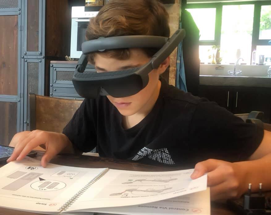 A young boy reads a book using electronic glasses. The large black digital glasses sitting over his eyes are attached to a band fit snugly around his head.