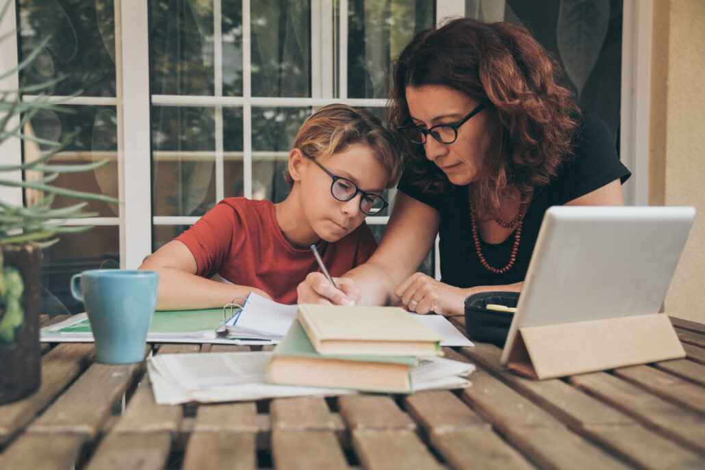 A mother and child work together with a laptop, books and papers. Both are wearing glasses.
