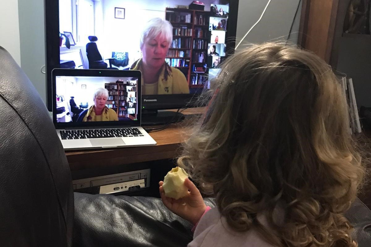 A three year old girl is pictured from behind, watching and listening to Lesley on a television and laptop screen as she reads a story. Lesley is wearing a yellow jumper with scarf. The child is wearing a pink top with rainbow cuffs.