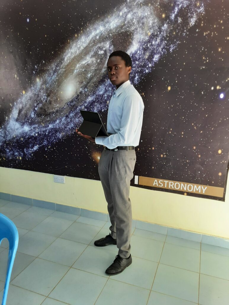 An African man in grey pants and a light collared shirt stands in front of a giant poster of a galaxy.