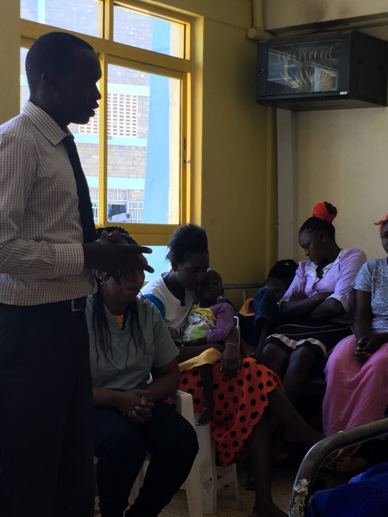 A doctor is standing and talking to a group of mothers who are sitting in chairs, some holding their young children. The room is painted yellow and they are sitting beside a big window.