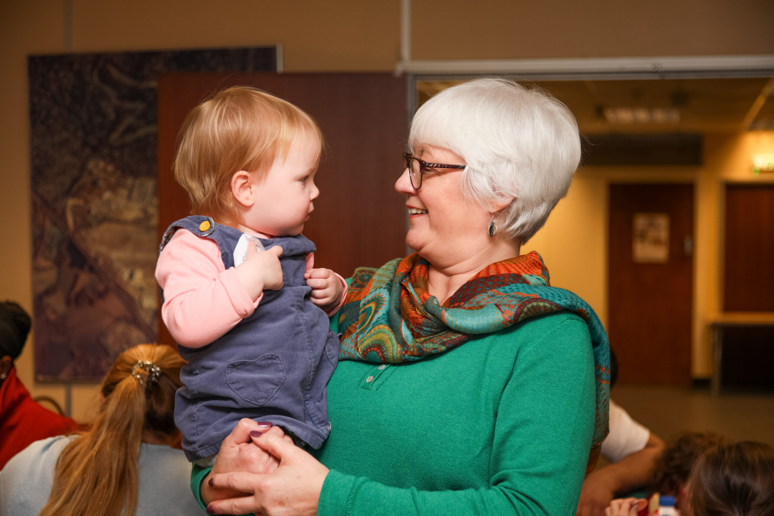 7. Lesley holds a young toddler at a family day. The toddler is looking directly at Lesley in a slightly quizzical way. Lesley is smiling and wearing a green jumper with green and orange scarf. Child is wearing a blue pinafore dress with pink jumper beneath.