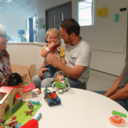 Lesley is sitting talking to a family in the hospital playroom. There are no other people in the frame. They are sitting at a round table, dad is holding his young son on his lap The child is wearing a Woody Toy Story character outfit, and laughing. Mum is sitting at the same table, wearing a green top and is laughing. Lesley is wearing a flowery top, is talking to the family and smiling. There are colourful toys on the table.