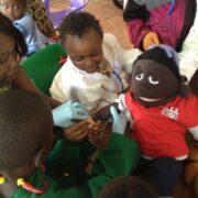 Young patients put a brannula in the arm of a medical play puppet. They are wearing surgical gloves.