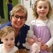 Sandra is pictured with two young children on EUA day. Mila is wearing a lilac tulle dress with a white long-sleeved shirt underneath, and white sandals. She is holding a pink unicorn and white teddy bear. Levi is wearing a white t-shirt and denim shorts, holding as soft lion toy. Sandra is squatting behind them, her arms wrapped around both children. She is wearing dark blue scrubs.