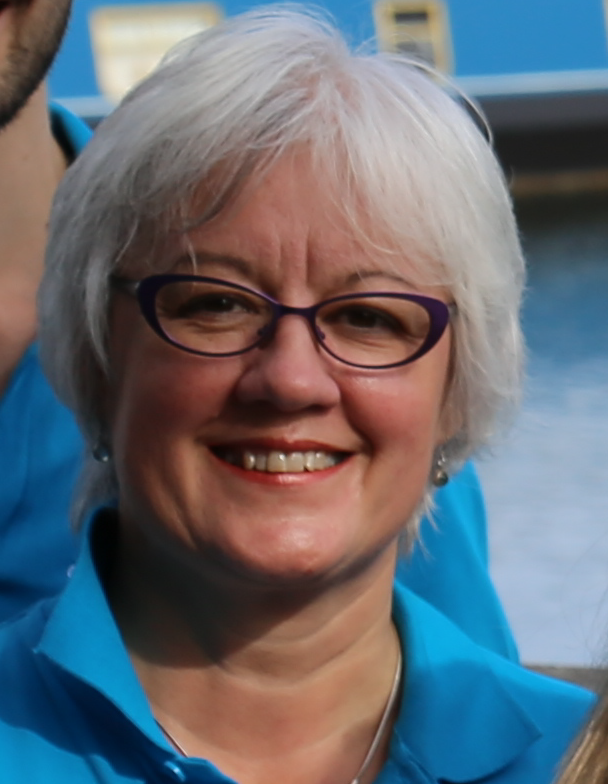 Lesley Geen is smiling. She ihas white hair and is wearing a blue top and glasses.