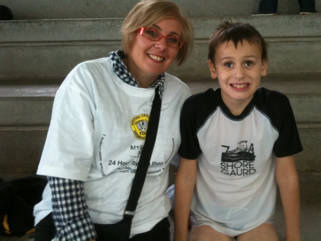 Sam Valavanis is wearing a blue and white swimming top, smiling broadly. Sandra is seated to his right wearing a blue checked shirt with a t-shirt over the top promoting the Beyond Sight Swim-a-thon fundraising event they are attending, signature bright red glasses in place and smiling.