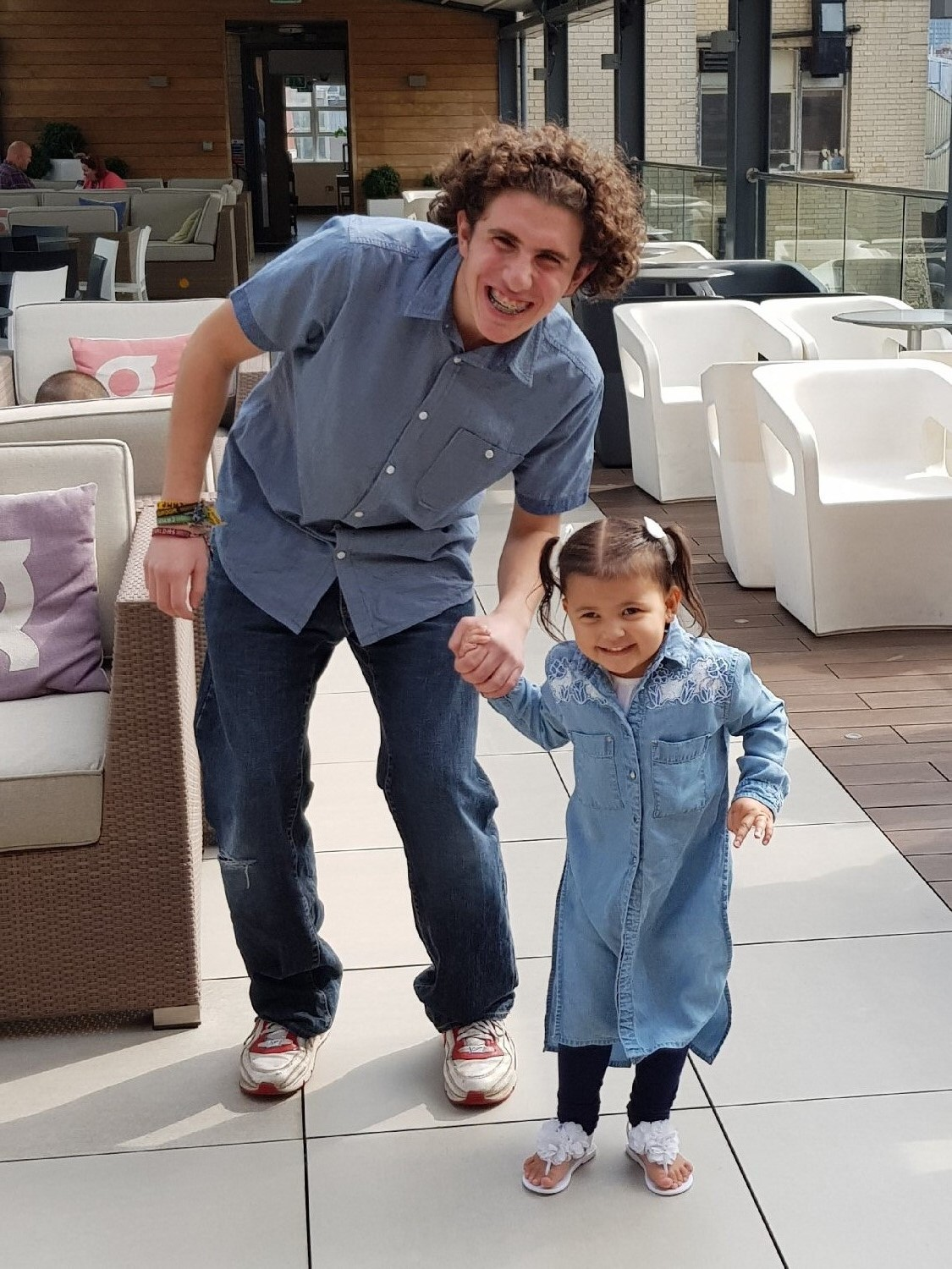 A toddler leads a teenager by the hand at a CHECT event. The teen is wearing jeans and a blue shirt. The toddler is wearing a blue denim dress. They both have wide smiles.