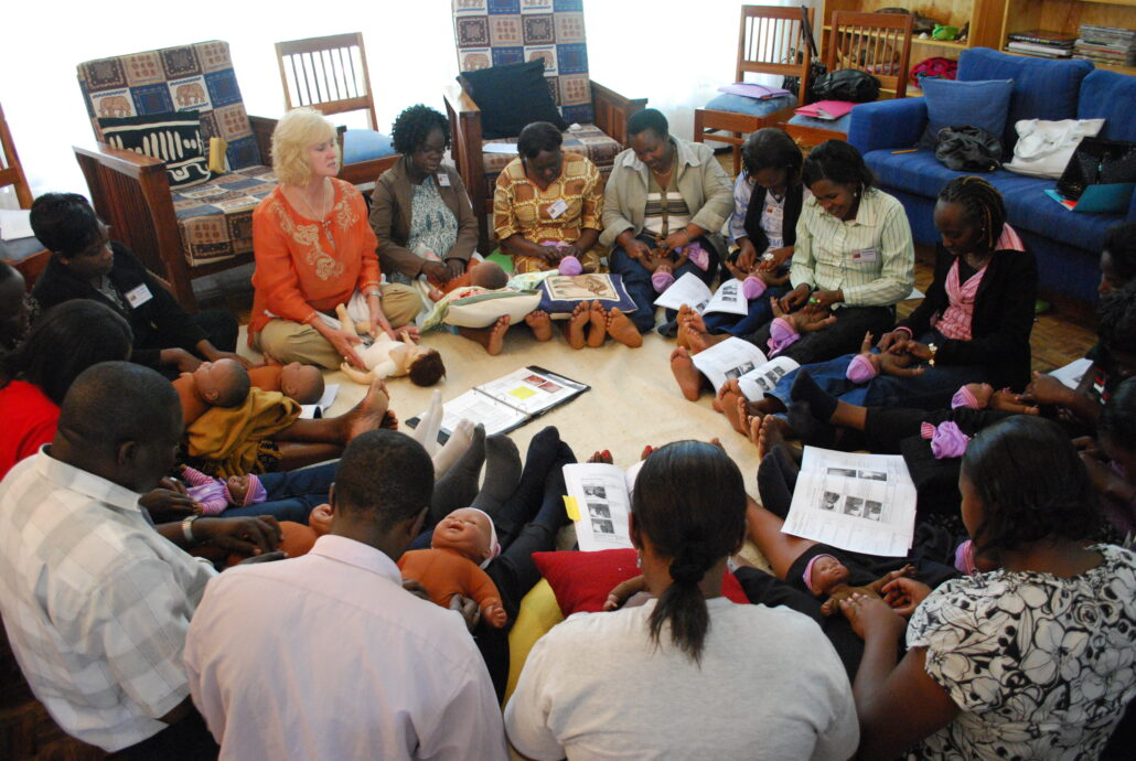 A large group of people is sitting on the floor in a circle facing inward, with legs outstretched. They are holding practice baby dolls on their laps as they practice infant massage strokes.