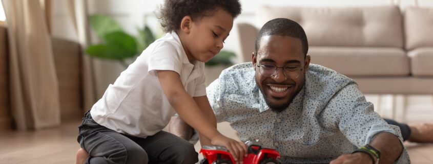 A black father smiles broadly as he and his happy son play toy cars together.