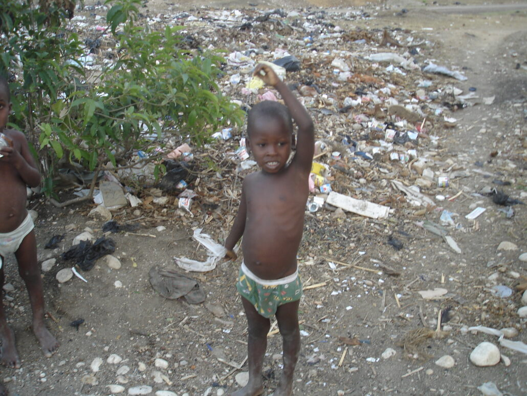 A young boy wearing patterned green underwear stands among the contents of a garbage dump, reaches his left hand above his head. In his hand is a short piece of string hanging down with a ripped piece of plastic tied to the end.