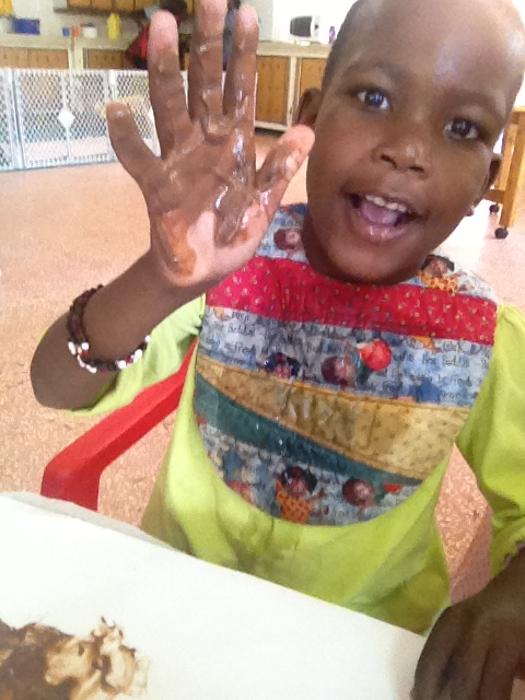 A young patient in Kenya has fun finger print painting with chocolate pudding.