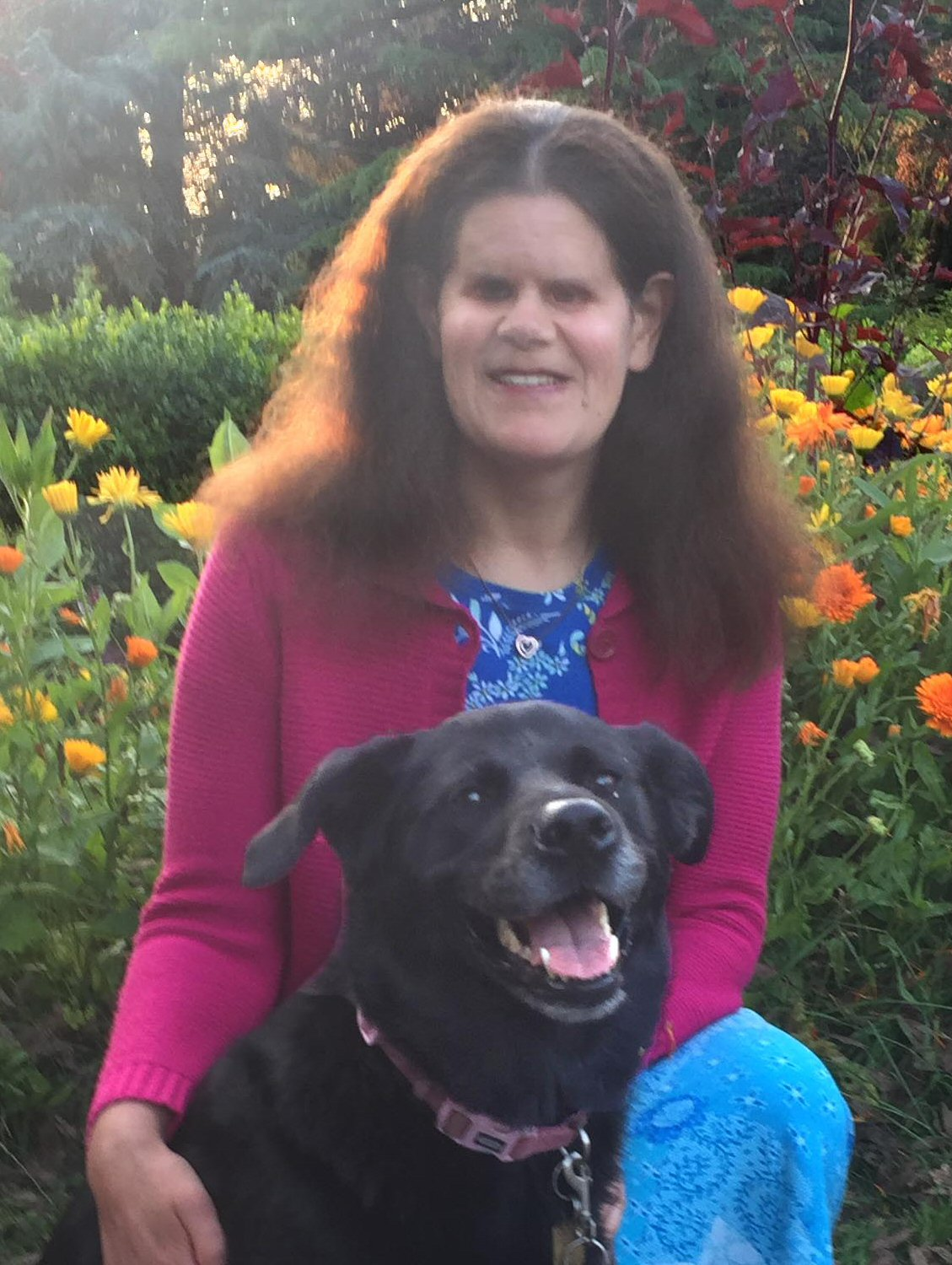 Abby is wearing a blue and white patterned top, dark pink collared cardigan, and light blue patterned skirt, and a heart necklace. She is pictured with her black german sheperd - golden retriever guide dog, who is wearing a pink collar with guide dor tag showing. Both are smiling broadly at the camera. The background is a bed of bright orange marigolds, a low hedge and tall trees.