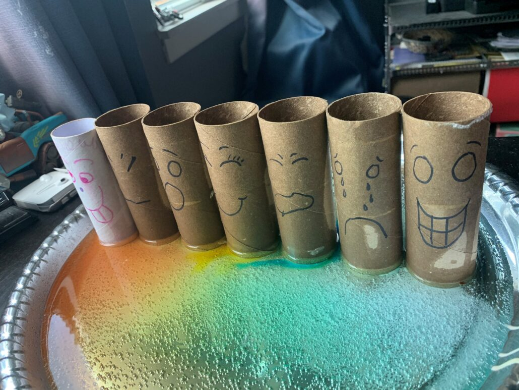 Seven cardboard tubes with different feelings faces drawn on them stand in a row on an edged tray, which is filled with a bright rainbow of liquid.