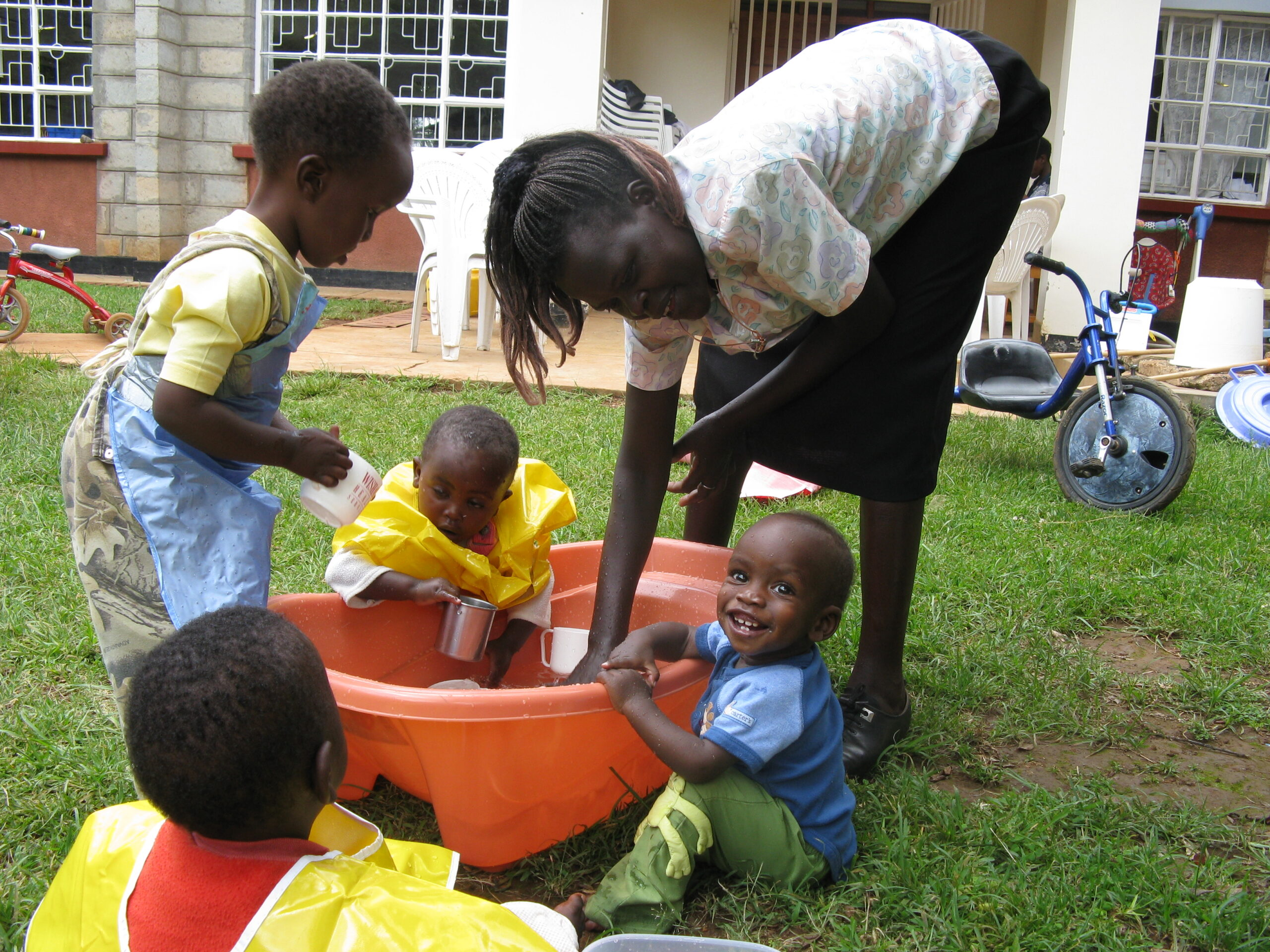 Several children of different ages and their adult helper are gathered around a big orange bowl filled with water, set on the grass in front of a building. They are having fun playing with various objects in the water.